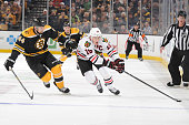 Jonathan Toews of the Chicago Blackhawks skates with the puck against Dennis Seidenberg of the Boston Bruins at the TD Garden on December 11 2014 in...