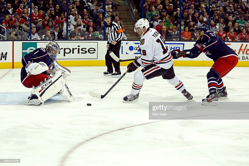 Jonathan Toews #19 of the Chicago Blackhawks slips past Adrian Aucoin #33 of the Columbus Blue Jackets and is able to score on Steve Mason #1 of the Columbus Blue Jackets on January 26, 2013 at Nationwide Arena in Columbus, Ohio. Chicago defeated Columbus 3-2.