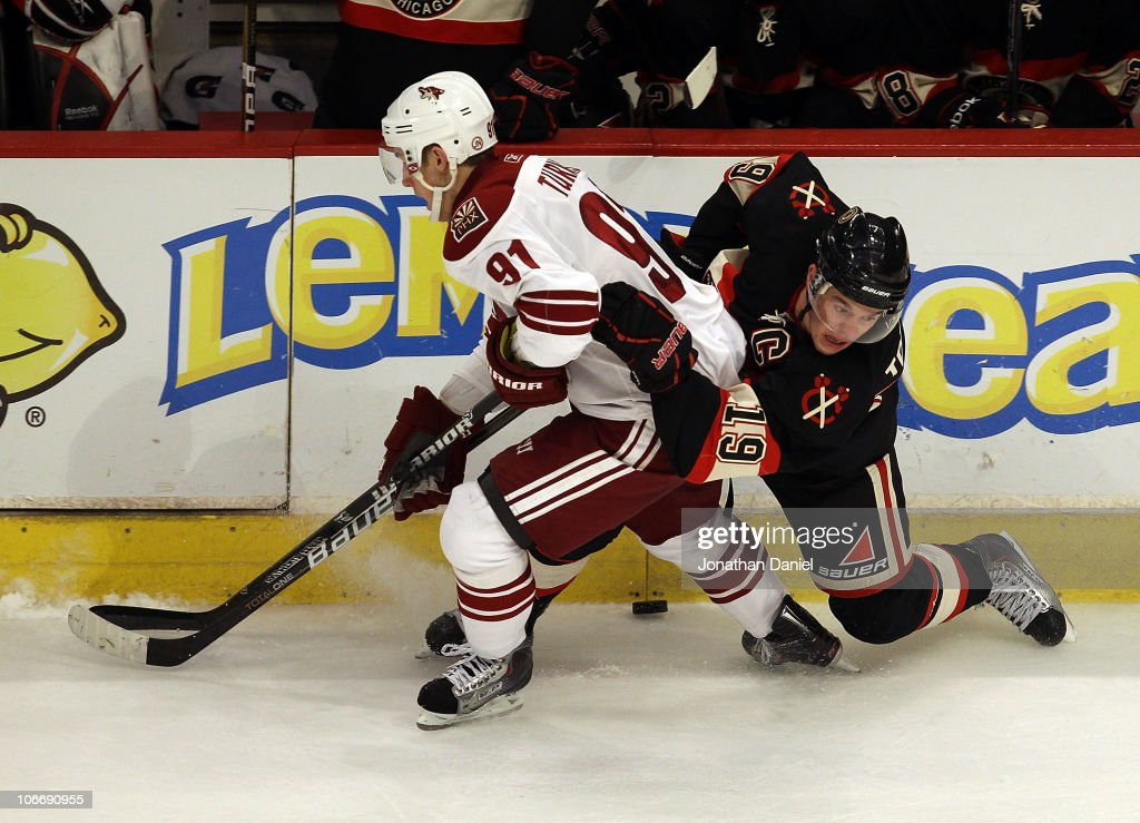 Jonathan Toews of the Chicago Blackhawks slips to the ice as he battles for the puck with Kyle Turris of the Phoenix Coyotes at the United Center on...