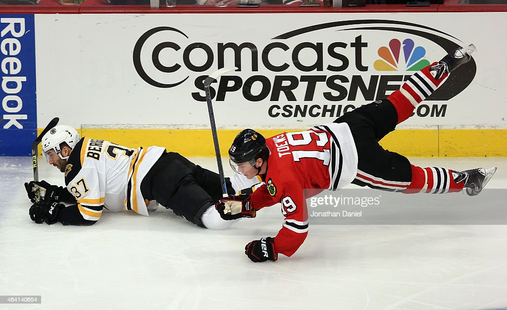 Jonathan Toews #19 of the Chicago Blackhawks slips to the ice while chasing Patrice Bergeron #37 of the Boston Bruins at the United Center on February 22, 2015 in Chicago, Illinois.
