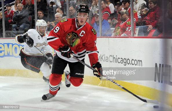 Jonathan Toews of the Chicago Blackhawks takes control of the puck as Francois Beauchemin of the Anaheim Ducks turns sharp around the boards during...