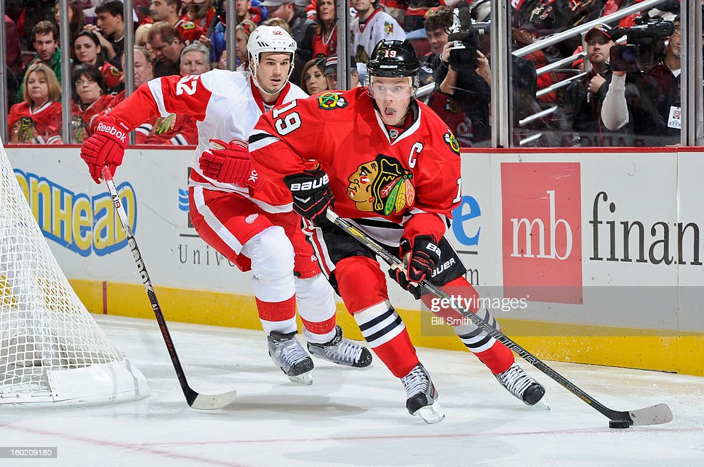 <a gi-track='captionPersonalityLinkClicked' href=/galleries/search?phrase=Jonathan+Toews&family=editorial&specificpeople=537799 ng-click='$event.stopPropagation()'>Jonathan Toews</a> #19 of the Chicago Blackhawks takes the puck around the net as <a gi-track='captionPersonalityLinkClicked' href=/galleries/search?phrase=Jonathan+Ericsson&family=editorial&specificpeople=2538498 ng-click='$event.stopPropagation()'>Jonathan Ericsson</a> #52 of the Detroit Red Wings follows behind during the NHL game on January 27, 2013 at the United Center in Chicago, Illinois.