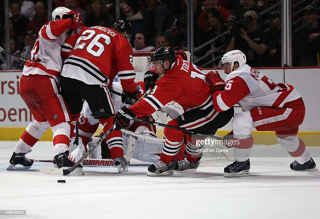 <a gi-track='captionPersonalityLinkClicked' href=/galleries/search?phrase=Jonathan+Toews&family=editorial&specificpeople=537799 ng-click='$event.stopPropagation()'>Jonathan Toews</a> #19 of the Chicago Blackhawks tries to control the puck under pressure from <a gi-track='captionPersonalityLinkClicked' href=/galleries/search?phrase=Niklas+Kronwall&family=editorial&specificpeople=220826 ng-click='$event.stopPropagation()'>Niklas Kronwall</a> #55 of the Detroit Red Wings at the United Center on April 12, 2013 in Chicago, Illinois. The Blackhawks defeated the Red Wings 3-2 in a shootout.