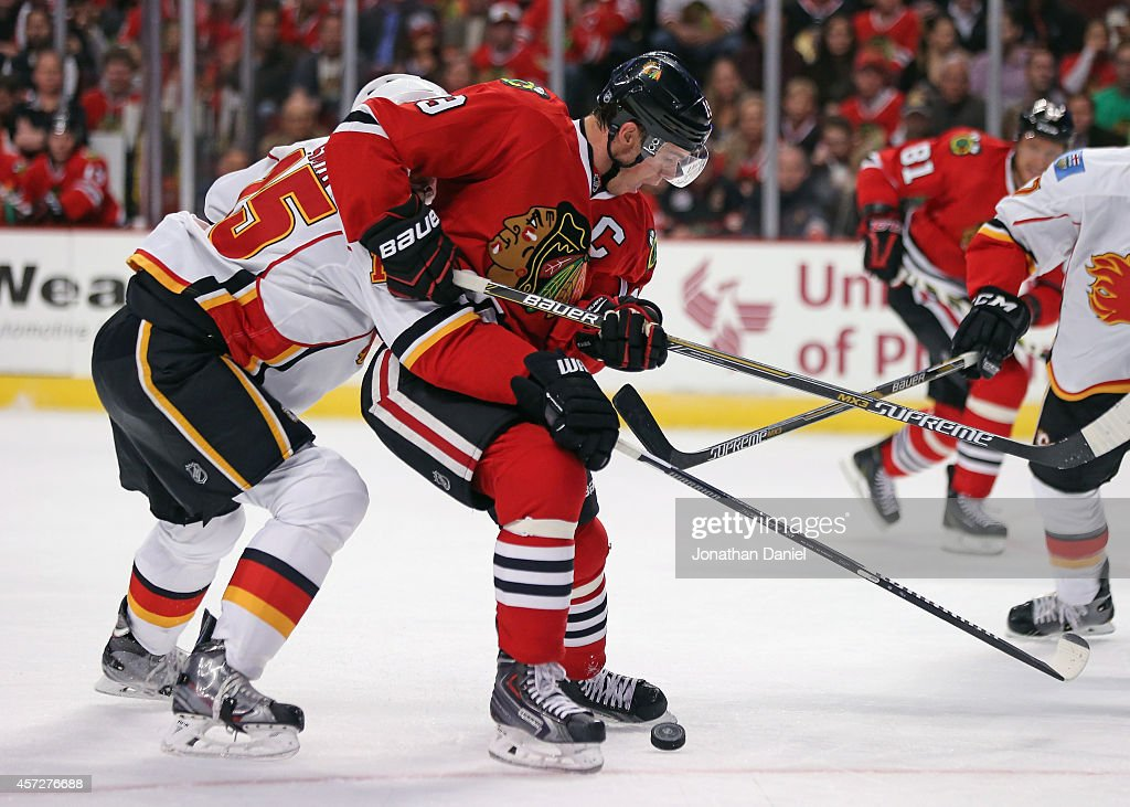 Jonathan Toews of the Chicago Blackhawks tries to control the puck under pressure from Ladislav Smid of the Calgary Flames at the United Center on...