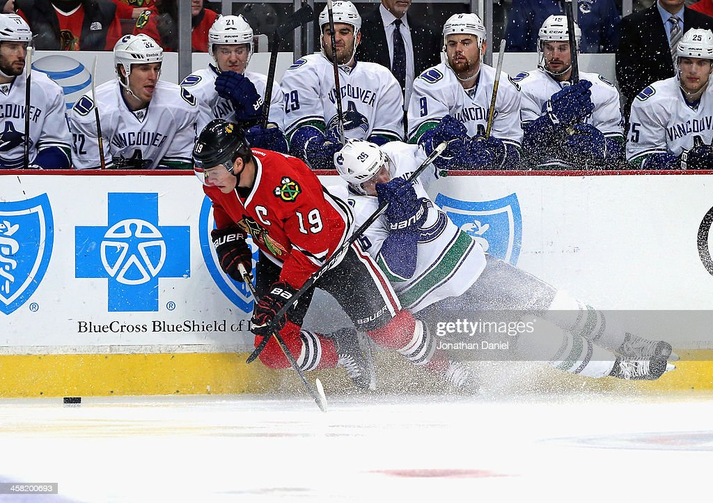 <a gi-track='captionPersonalityLinkClicked' href=/galleries/search?phrase=Jonathan+Toews&family=editorial&specificpeople=537799 ng-click='$event.stopPropagation()'>Jonathan Toews</a> #19 of the Chicago Blackhawks tries to control the puck from his knees as <a gi-track='captionPersonalityLinkClicked' href=/galleries/search?phrase=Jannik+Hansen&family=editorial&specificpeople=741716 ng-click='$event.stopPropagation()'>Jannik Hansen</a> #36 of the Vancouver Canucks hits the ice at the United Center on December 20, 2013 in Chicago, Illinois.