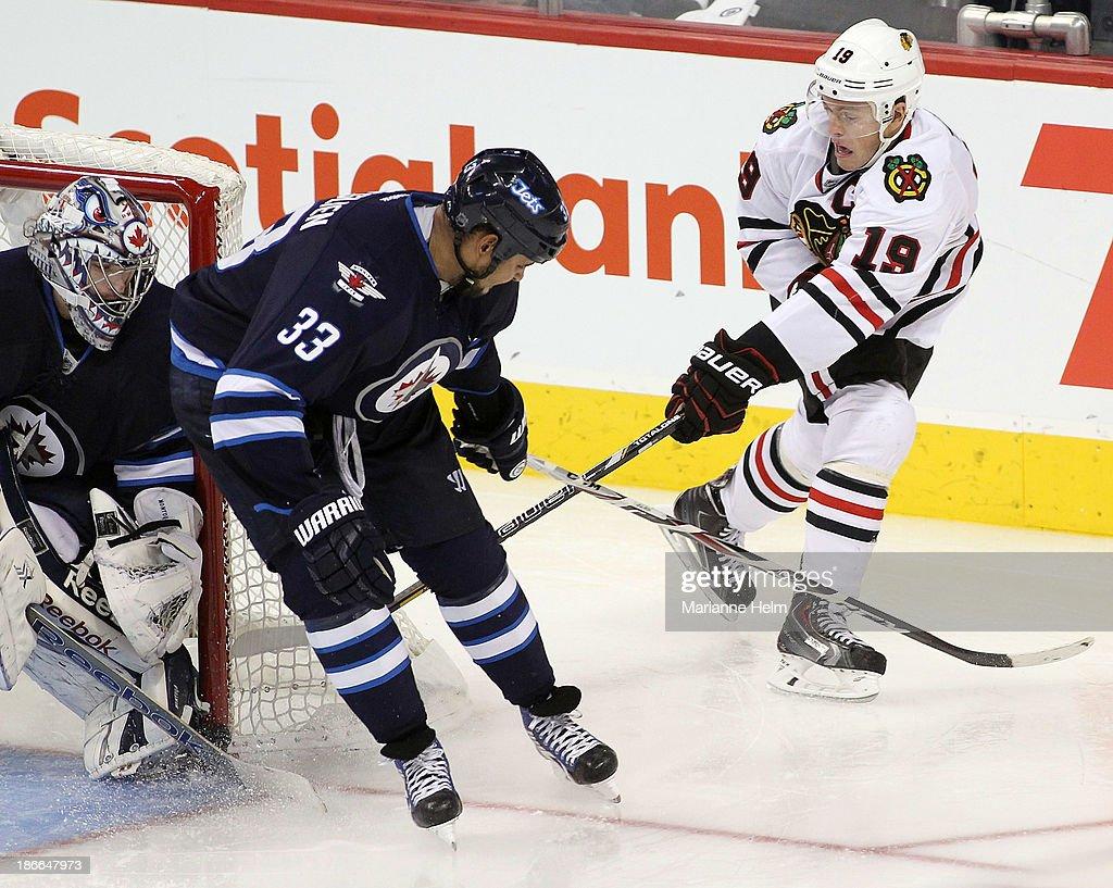 <a gi-track='captionPersonalityLinkClicked' href=/galleries/search?phrase=Jonathan+Toews&family=editorial&specificpeople=537799 ng-click='$event.stopPropagation()'>Jonathan Toews</a> #19 of the Chicago Blackhawks tries to get the puck past <a gi-track='captionPersonalityLinkClicked' href=/galleries/search?phrase=Dustin+Byfuglien&family=editorial&specificpeople=672505 ng-click='$event.stopPropagation()'>Dustin Byfuglien</a> #33 and <a gi-track='captionPersonalityLinkClicked' href=/galleries/search?phrase=Al+Montoya&family=editorial&specificpeople=213916 ng-click='$event.stopPropagation()'>Al Montoya</a> #35 of the Winnipeg Jets in third period action in an NHL game at the MTS Centre on November 2, 2013 in Winnipeg, Manitoba, Canada.