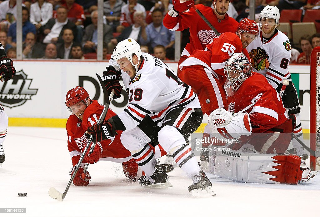 <a gi-track='captionPersonalityLinkClicked' href=/galleries/search?phrase=Jonathan+Toews&family=editorial&specificpeople=537799 ng-click='$event.stopPropagation()'>Jonathan Toews</a> #19 of the Chicago Blackhawks tries to get to the puck in front of <a gi-track='captionPersonalityLinkClicked' href=/galleries/search?phrase=Jimmy+Howard&family=editorial&specificpeople=2118637 ng-click='$event.stopPropagation()'>Jimmy Howard</a> #35 and <a gi-track='captionPersonalityLinkClicked' href=/galleries/search?phrase=Daniel+Cleary&family=editorial&specificpeople=220490 ng-click='$event.stopPropagation()'>Daniel Cleary</a> #11 of the Detroit Red Wings during the third period in Game Three of the Western Conference Semifinals during the 2013 NHL Stanley Cup Playoffs at Joe Louis Arena on May 20, 2013 in Detroit, Michigan. Detroit won the game 3-1 to take a 2-1 series lead.