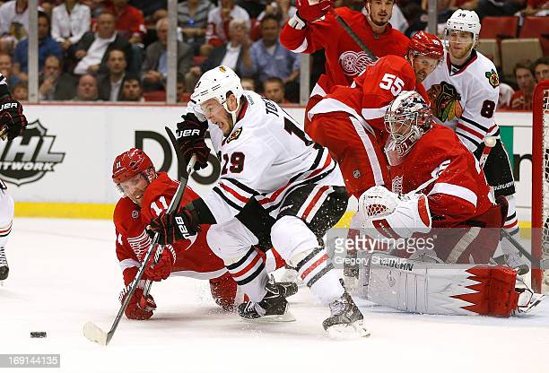 Jonathan Toews of the Chicago Blackhawks tries to get to the puck in front of Jimmy Howard and Daniel Cleary of the Detroit Red Wings during the...