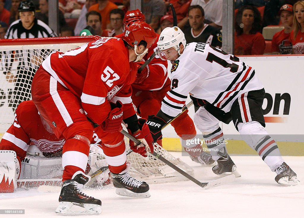 <a gi-track='captionPersonalityLinkClicked' href=/galleries/search?phrase=Jonathan+Toews&family=editorial&specificpeople=537799 ng-click='$event.stopPropagation()'>Jonathan Toews</a> #19 of the Chicago Blackhawks tries to jam home a third period shot next to <a gi-track='captionPersonalityLinkClicked' href=/galleries/search?phrase=Jonathan+Ericsson&family=editorial&specificpeople=2538498 ng-click='$event.stopPropagation()'>Jonathan Ericsson</a> #52 of the Detroit Red Wings in Game Three of the Western Conference Semifinals during the 2013 NHL Stanley Cup Playoffs at Joe Louis Arena on May 20, 2013 in Detroit, Michigan. Detroit won the game 3-1 to take a 2-1 series lead.