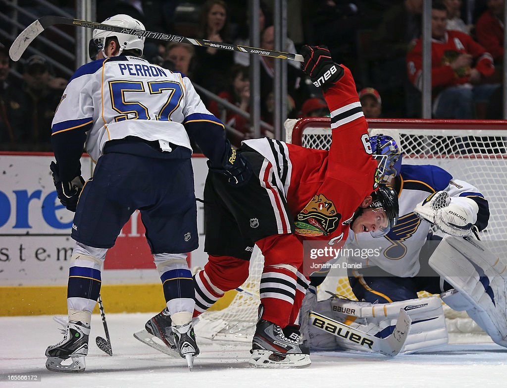 Jonathan Toews #19 of the Chicago Blackhawks tries to keep his balance between David Perron #57 and Brian Elliott #1 of the St. Louis Blues at the United Center on April 4, 2013 in Chicago, Illinois. The Blues defeated the Blackhawks 4-3 in a shootout.