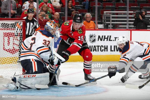 Jonathan Toews of the Chicago Blackhawks works to get at the puck next to goalie Cam Talbot of the Edmonton Oilers as Kris Russell reaches in from...