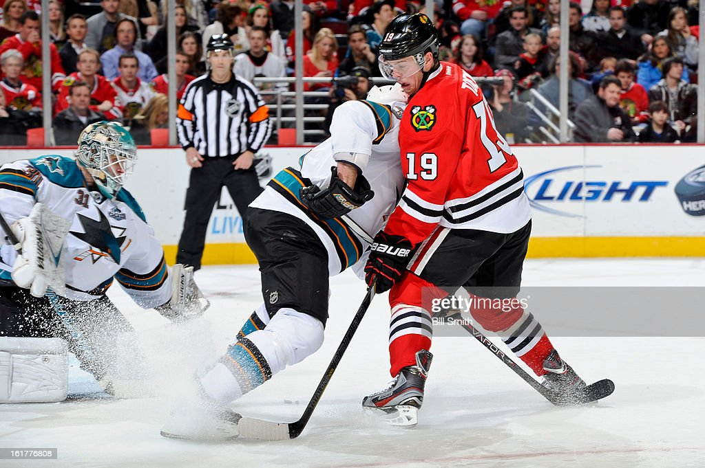 Jonathan Toews #19 of the Chicago Blackhawks works to get the puck away from the San Jose Sharks while in front of Sharks goalie Antti Niemi #31 during the NHL game on February 15, 2013 at the United Center in Chicago, Illinois.