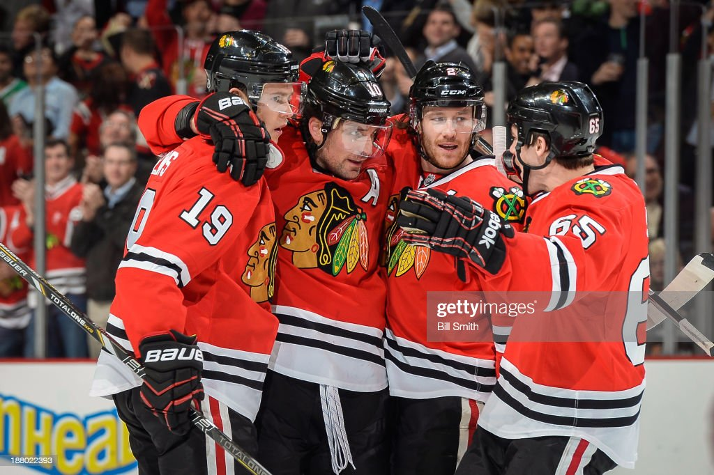 Jonathan Toews #19, Patrick Sharp #10, Duncan Keith #2 and Andrew Shaw #65 of the Chicago Blackhawks celebrate after Sharp scored against the Phoenix Coyotes in the first period during the NHL game on November 14, 2013 at the United Center in Chicago, Illinois.
