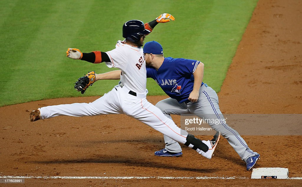 Jonathan Villar #6 of the Houston Astros leaps safely into first base in the second inning as Adam Lind #26 of the Toronto Blue Jays cannot make the play at Minute Maid Park on August 24, 2013 in Houston, Texas.