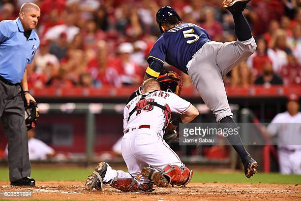 Jonathan Villar of the Milwaukee Brewers collides with catcher Tucker Barnhart of the Cincinnati Reds after being tagged out at home plate in the...
