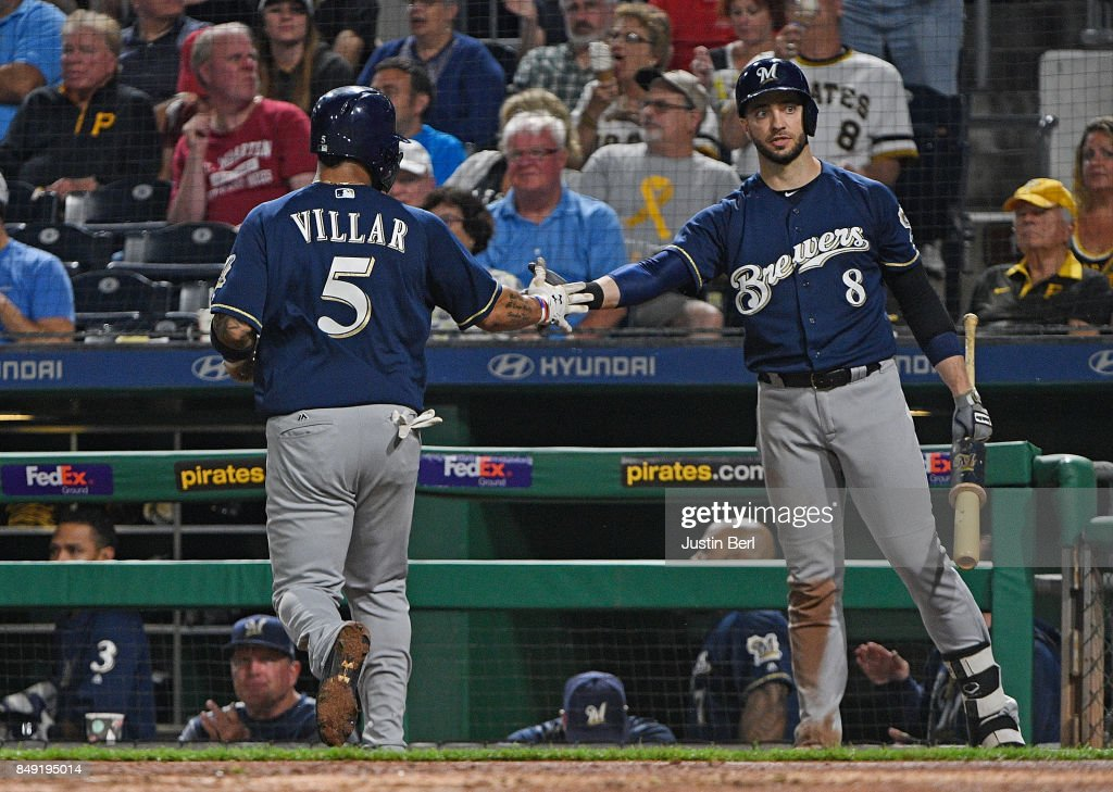 Jonathan Villar #5 of the Milwaukee Brewers is greeted by Ryan Braun #8 after coming around to score on an RBI single by Neil Walker #15 in the sixth inning during the game against the Pittsburgh Pirates at PNC Park on September 18, 2017 in Pittsburgh, Pennsylvania.