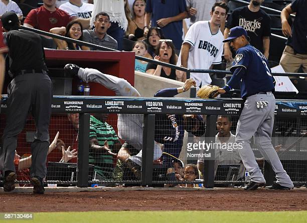 Jonathan Villar of the Milwaukee Brewers makes a diving catch over the railing in front of teammate Orlando Arcia on a pop foul by Tuffy Gosewisch of...