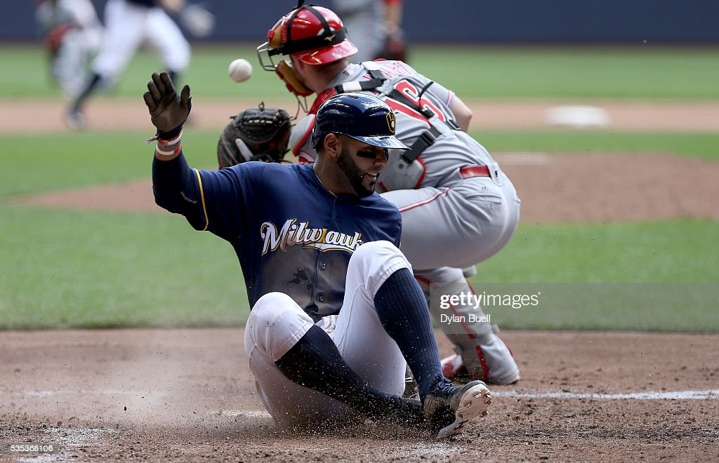 Jonathan Villar of the Milwaukee Brewers slides into home plate to score a run past Tucker Barnhart of the Cincinnati Reds in the third inning at...