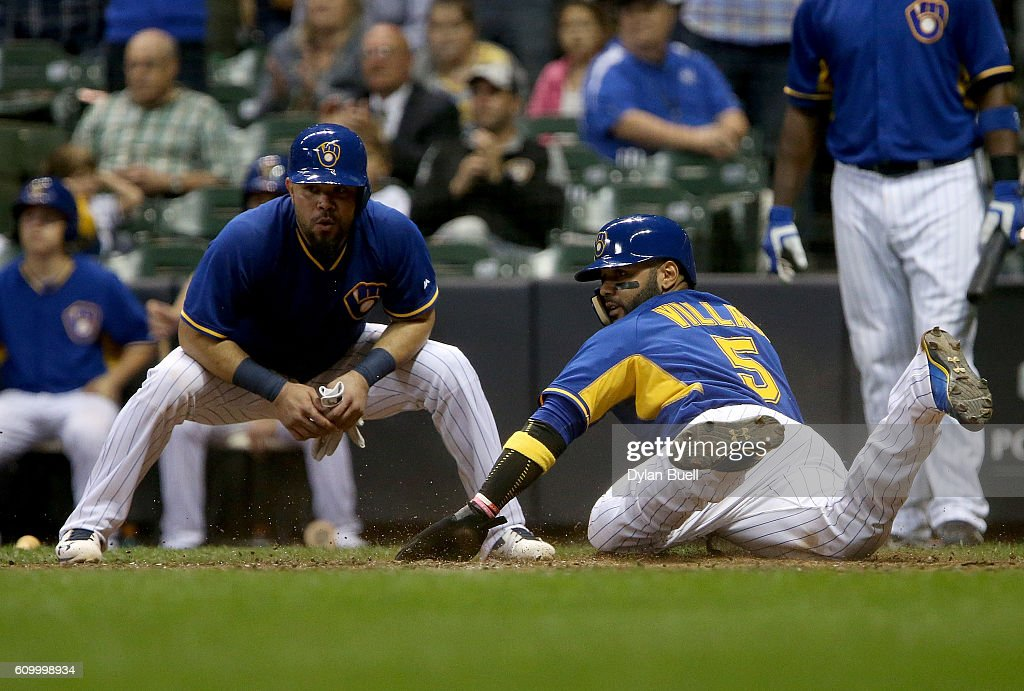 Jonathan Villar #5 of the Milwaukee Brewers slides into home to score a run as teammate Josmil Pinto #21 looks on in the seventh inning against the Cincinnati Reds at Miller Park on September 23, 2016 in Milwaukee, Wisconsin.