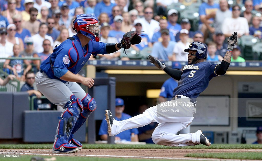 Jonathan Villar of the Milwaukee Brewers slides into home to score against David Ross of the Chicago Cubs in the first inning at Miller Park on July...