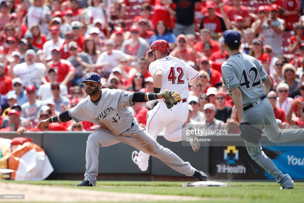 Jonathan Villar #5 of the Milwaukee Brewers takes the throw while covering first base ahead of Tucker Barnhart #16 of the Cincinnati Reds in the second inning of the game at Great American Ball Park on April 15, 2017 in Cincinnati, Ohio. The Reds defeated the Brewers 7-5. All players are wearing #42 in honor of Jackie Robinson Day.