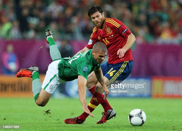Jonathan Walters of Republic of Ireland clashes with Xabi Alonso of Spain during the UEFA EURO 2012 group C match between Spain and Ireland at The...