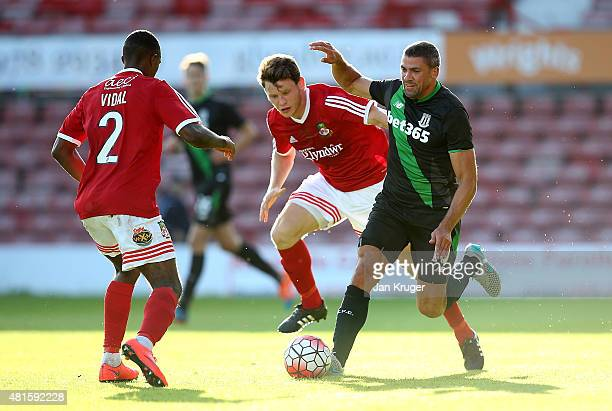 Jonathan Walters of Stoke City battles with Connor Jennings of Wrexham during the pre season friendly match between Wrexham and Stoke City at...