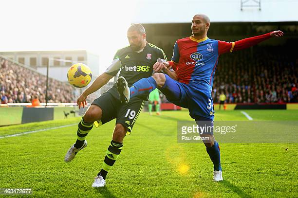 Jonathan Walters of Stoke City is challenged by Adlene Guedioura of Crystal Palace during the Barclays Premier League match between Crystal Palace...