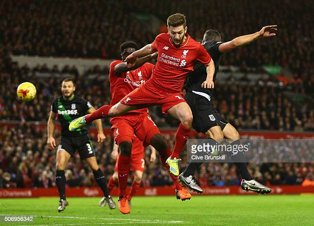 Jonathan Walters of Stoke City jumps with Adam Lallana and Kolo Toure of Liverpool during the Capital One Cup semi final second leg match between...