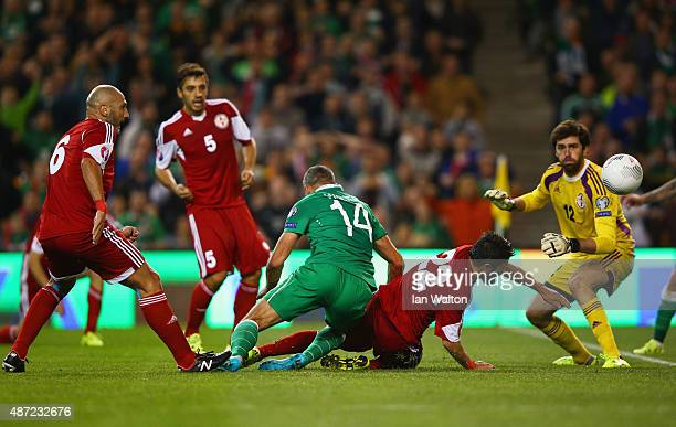 Jonathan Walters of the Republic of Ireland beats Giorgi Navalovski and goalkeeper Nukri Revishvili of Georgia to score their first goal during the...
