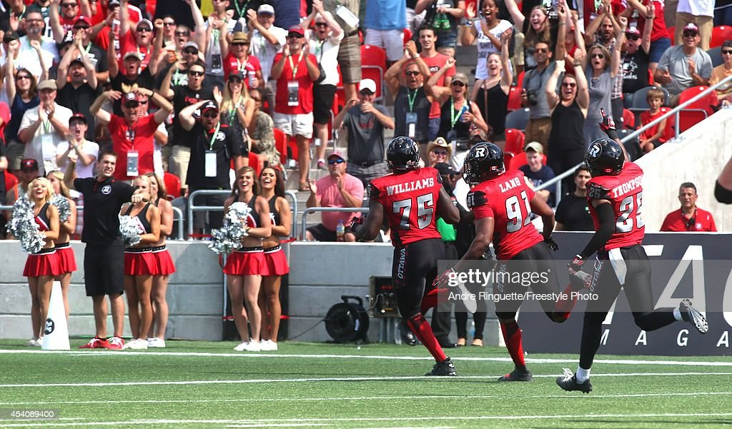 Jonathan Williams #75 of the Ottawa Redblacks returns a 1st quarter interception against the Calgary Stampeders as teammates Brandon Lang #91 and Brandyn Thompson #25 follow on the play during a CFL game at TD Place Stadium on August 24, 2014 in Ottawa, Ontario, Canada.