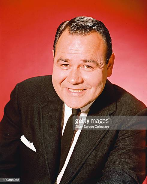 Jonathan Winters US actor and comedian wearing a black jacket white shirt and black tie in a studio portrait against a red blackground circa 1960