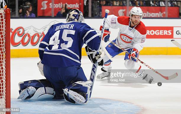 Jonathon Bernier of the Toronto Maple Leafs defends the goal as David Desharnais of the Montreal Canadiens looks to shoot the puck in their NHL...