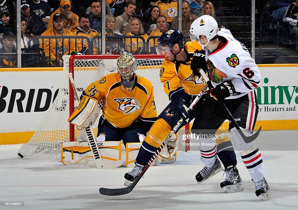 Jonathon Blum #7 of the Nashville Predators and Marcus Kruger #16 of the Chicago Blackhawks watch a puck go wide of Predators goalie Pekka Rinne #35 at the Bridgestone Arena on February 10, 2013 in Nashville, Tennessee.