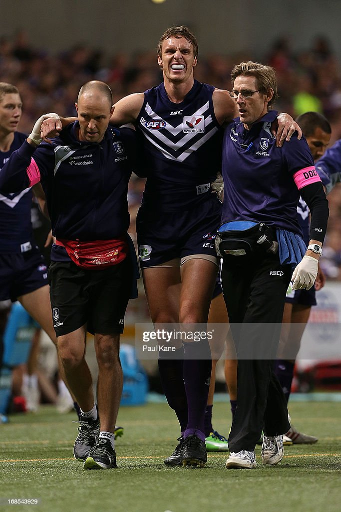 Jonathon Griffin of the Dockers is assisted from the field after injuring his knee during the round seven AFL match between the Fremantle Dockers and the Collingwood Magpies at Patersons Stadium on May 11, 2013 in Perth, Australia.
