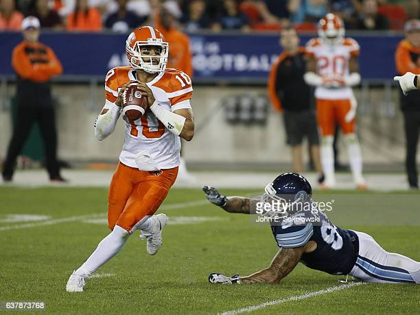 Jonathon Jennings of the BC Lions looks to pass the ball after eluding a tackle by Ricky Foley of the Toronto Argonauts during a CFL game at BMO...