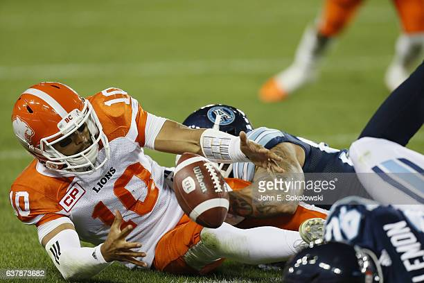 Jonathon Jennings of the BC Lions recovers his own fumble after being hit by Rickey Foley of the Toronto Argonauts during a CFL game at BMO field on...