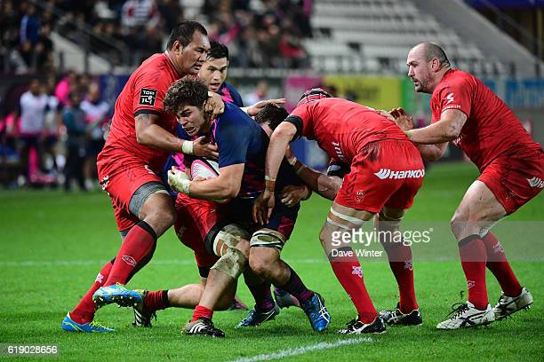Jonathon Ross of Stade Francais Paris tries to squeeze through the Stade Francais Paris defence during the French Top 14 between Stade Francais and...