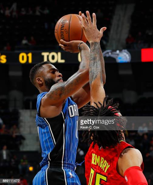 Jonathon Simmons of the Orlando Magic attempts a shot over DeAndre' Bembry of the Atlanta Hawks at Philips Arena on December 9 2017 in Atlanta...