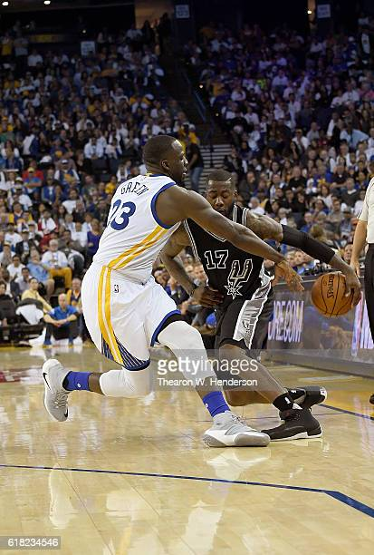 Jonathon Simmons of the San Antonio Spurs dribbles the ball while guarded by Draymond Green of the Golden State Warriors during the third quarter in...