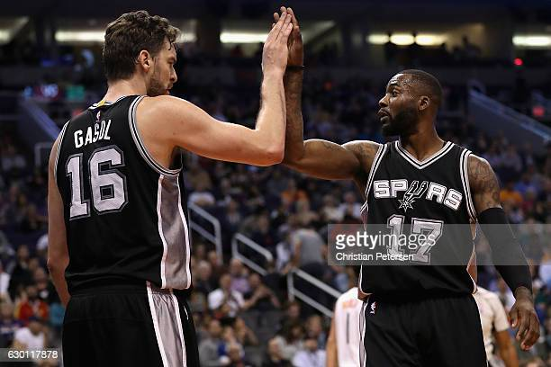 Jonathon Simmons of the San Antonio Spurs high fives Pau Gasol during the NBA game against the Phoenix Suns at Talking Stick Resort Arena on December...