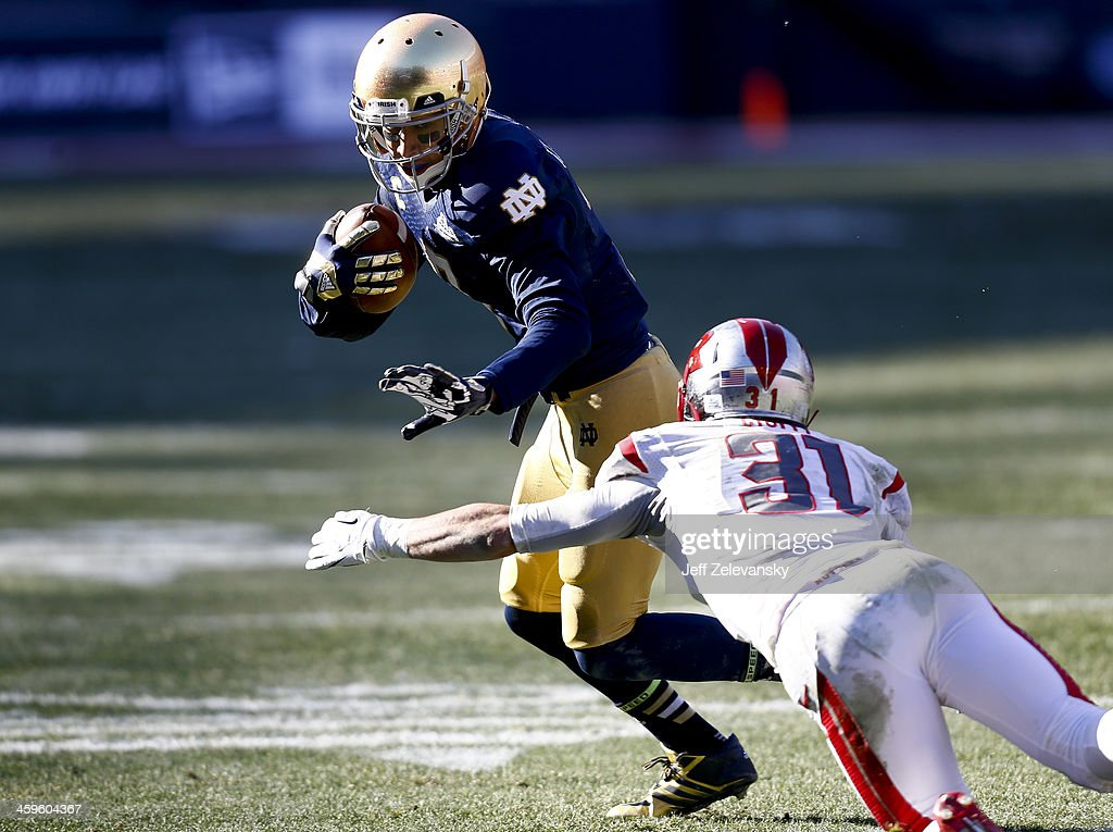 TJ Jones #7 of the Notre Dame Fighting Irish dodges Anthony Cioffi #31 of the Rutgers Scarlet Knights during the New Era Pinstripe Bowl at Yankee Stadium on December 28, 2013 in the Bronx borough of New York City.