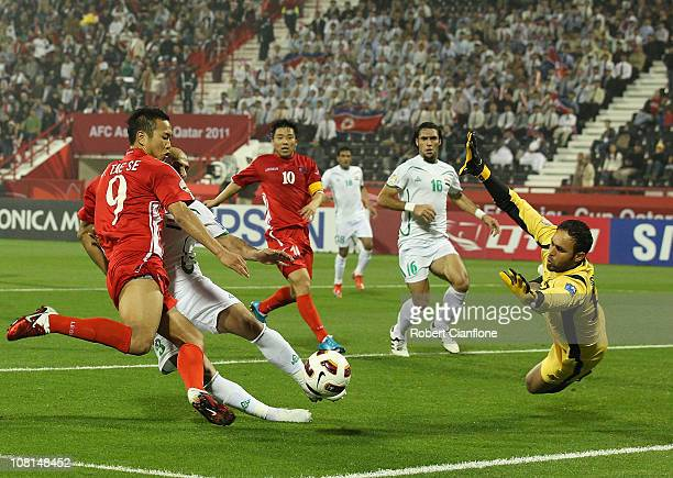 Jong Tae Se of DPR Korea has his shot on goal spoiled by Basem Abbas of Iraq and goalkeeper Mohammed Kassid during the AFC Asian Cup Group D match...