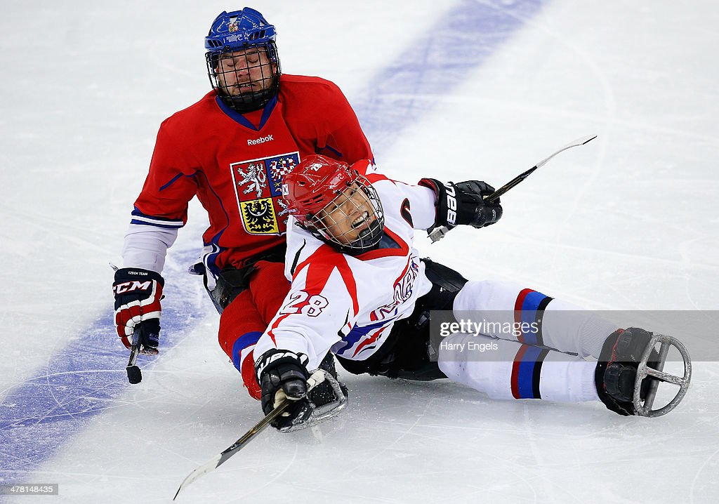 Jong-Kyung Lee of Korea (R) collides with Michal Geier of Czech Republic during the Ice Sledge Hockey Classification match between the Czech Republic and Korea at the Shayba Arena during day five of the 2014 Paralympic Winter Games on March 12, 2014 in Sochi, Russia.