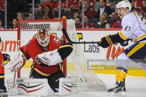 Joni Ortio of the Calgary Flames stops the shot of Colin Wilson of the Nashville Predators during an NHL game at Scotiabank Saddledome on March 21...