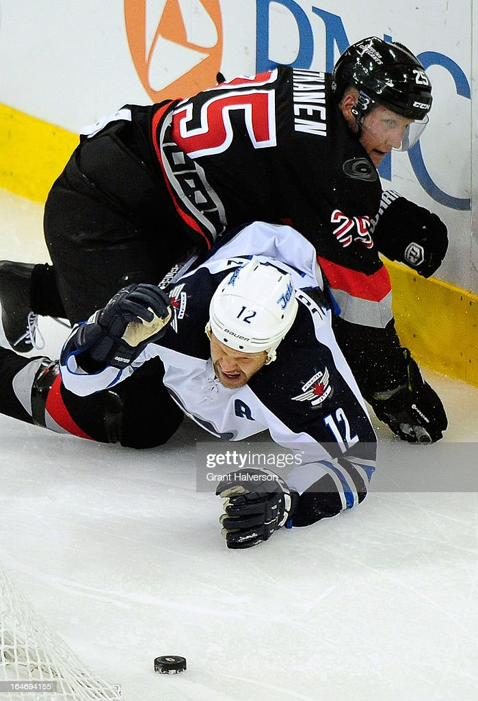 <a gi-track='captionPersonalityLinkClicked' href=/galleries/search?phrase=Joni+Pitkanen&family=editorial&specificpeople=204480 ng-click='$event.stopPropagation()'>Joni Pitkanen</a> #25 of the Carolina Hurricanes knocks <a gi-track='captionPersonalityLinkClicked' href=/galleries/search?phrase=Olli+Jokinen&family=editorial&specificpeople=202946 ng-click='$event.stopPropagation()'>Olli Jokinen</a> #12 of the Winnipeg Jets to the ice during play at PNC Arena on March 26, 2013 in Raleigh, North Carolina. Winnipeg won 4-1.