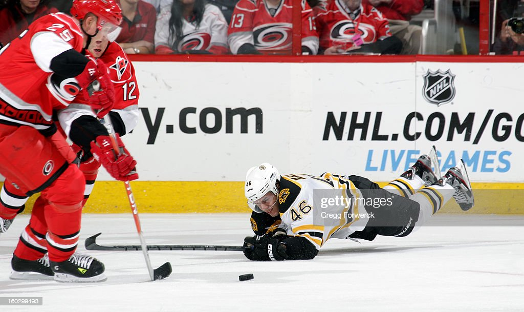 Joni Pitkanen #25 of the Carolina Hurricanes moves in to collect the puck as David Krejci #46 of the Boston Bruins crashes to the ice during their NHL game on January 28, 2013 at PNC Arena in Raleigh North Carolina.