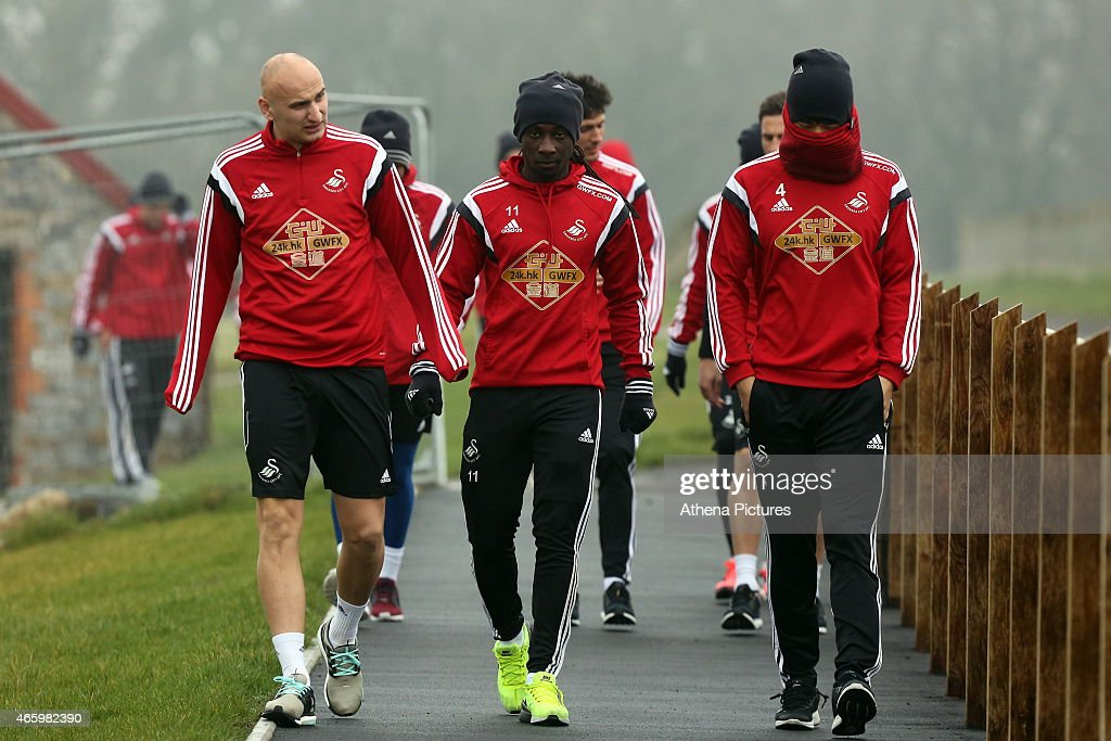 L-R Jonjo Shelvey, Marvin Emnes and Ki Sung Yueng walk to the pitch prior to the Swansea City training session at Fairwood Training Ground on March 12, 2015 in Swansea, Wales.