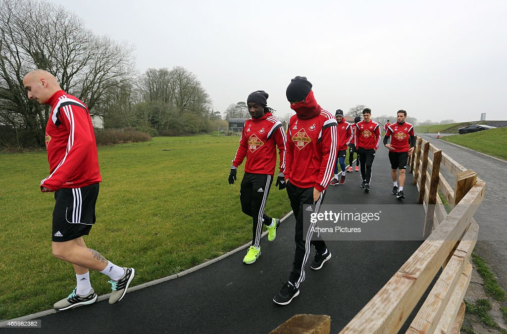 Jonjo Shelvey, Marvin Emnes, Ki Sung Yueng, Neil Taylor, Jack Cork and Angel Rangel walk to the pitch prior to the Swansea City training session at Fairwood Training Ground on March 12, 2015 in Swansea, Wales.