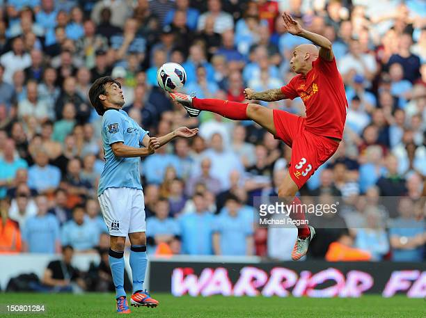 Jonjo Shelvey of Liverpool competes with David Silva of Manchester City during the Barclays Premier League match between Liverpool and Manchester...